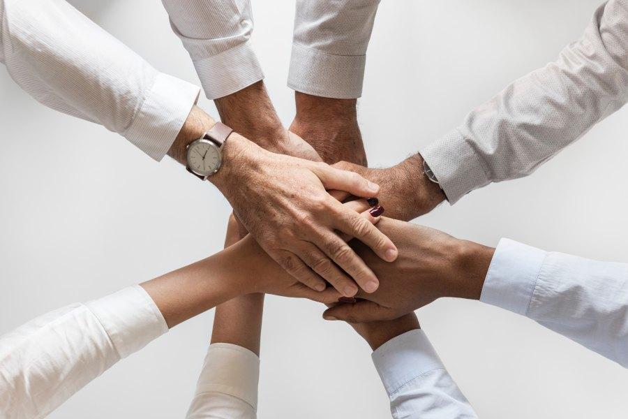 ihmisten kädet yhteen liitettynä keskellä kuvaa