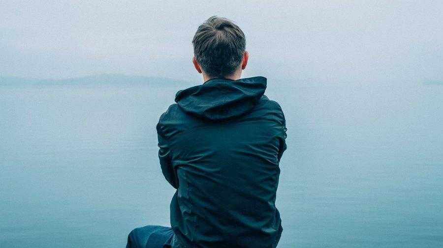 mies istuu ja katsoo merelle