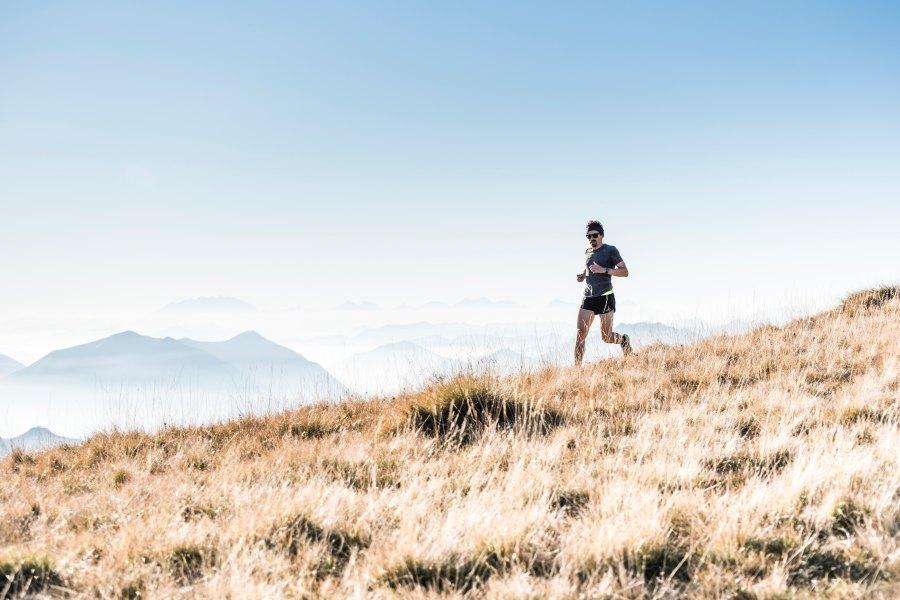 mies juoksee vuoren rinnettä
